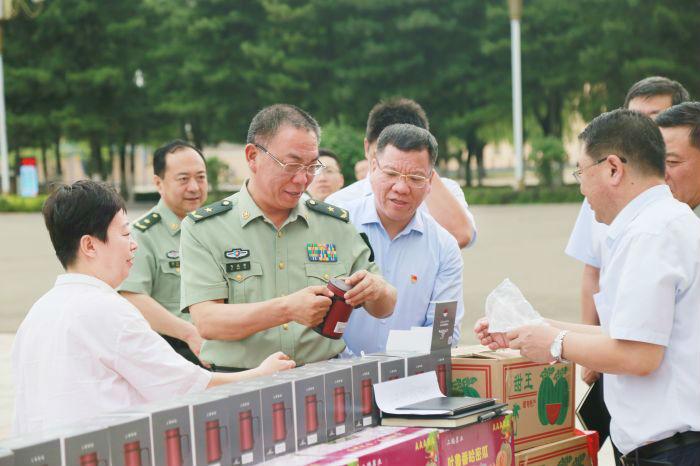中国银行内蒙古分行行长陈志能向内蒙古军区司令员马庆雷介绍展示拥军慰问品